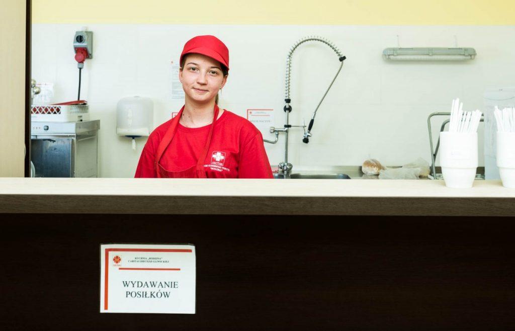 Pracownica Caritas za ladą w jadłodalnii